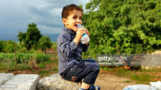 portrait of smiling boy drinking water from bottle while sitting on rock - イラク ストックフォトと画像