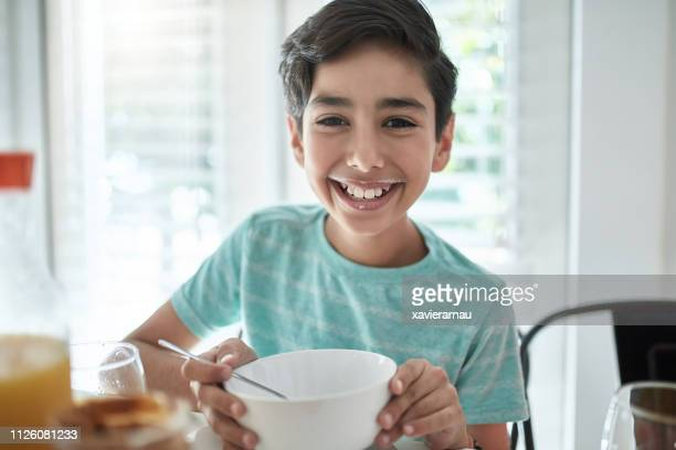 portrait of smiling boy having breakfast at home - pre adolescent child stock pictures, royalty-free photos & images