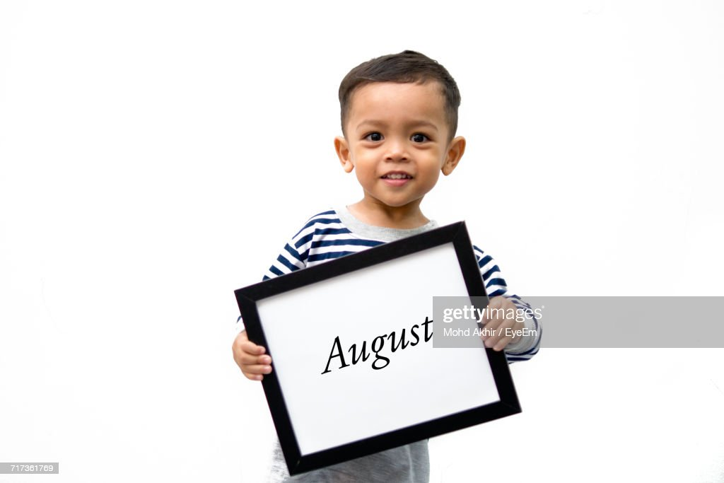 Portrait Of Smiling Boy Holding Frame With August Text Against White ...