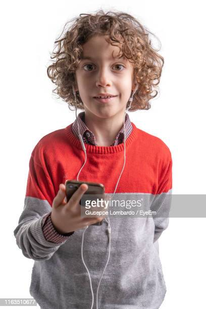 portrait of smiling boy holding phone while wearing headphones against white background - only boys stock pictures, royalty-free photos & images