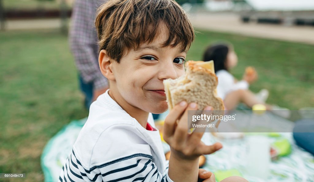 Portrait of smiling boy holding sandwich with his family in background : Foto de stock