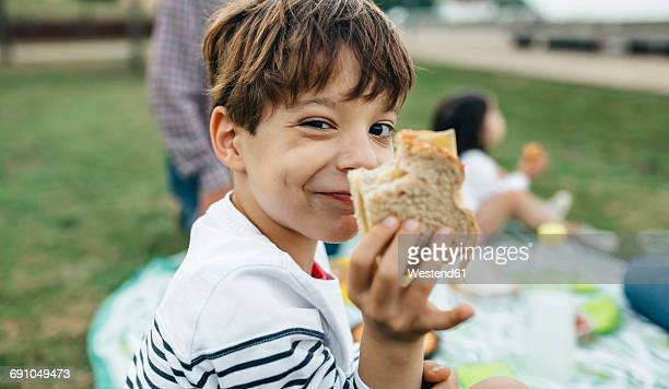 portrait of smiling boy holding sandwich with his family in background - picknick stock-fotos und bilder