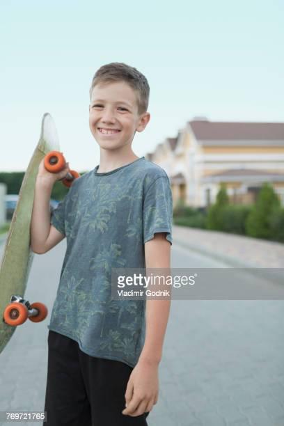 portrait of smiling boy holding skateboard while standing on street - sorriso aberto imagens e fotografias de stock
