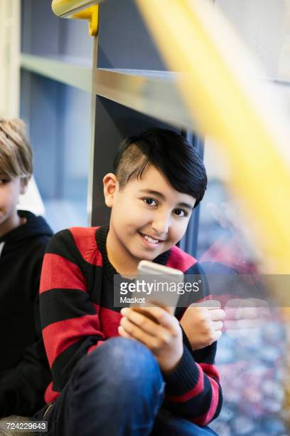 Portrait of smiling boy holding smart phone in middle school