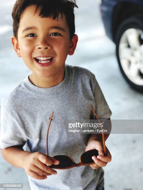 portrait of smiling boy holding sunglasses - meghan stock photos and pictures