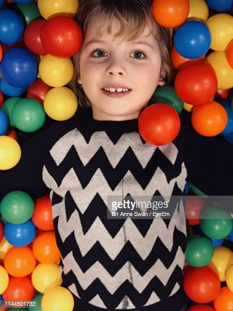 portrait of smiling boy in ball pool - brianne stock pictures, royalty-free photos & images