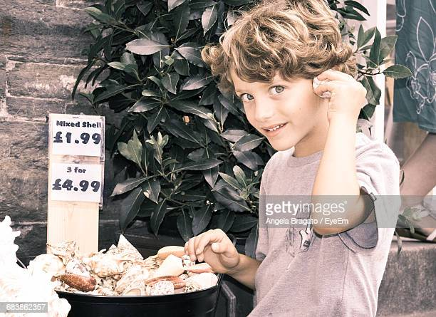 Portrait Of Smiling Boy Listening To Seashell At Market Stall