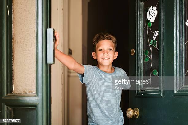 Portrait of smiling boy opening door