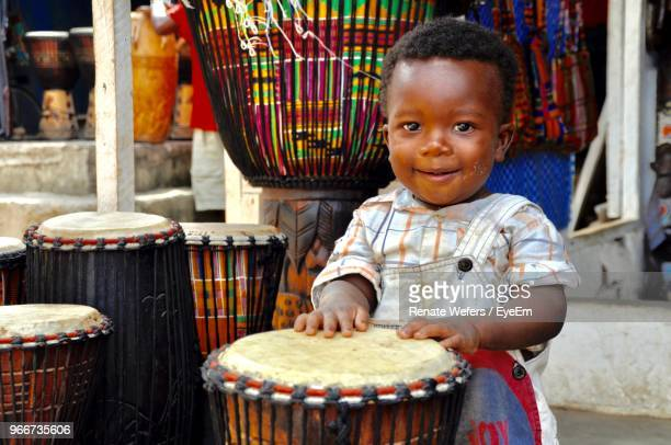 portrait of smiling boy playing drum - ghana africa fotografías e imágenes de stock