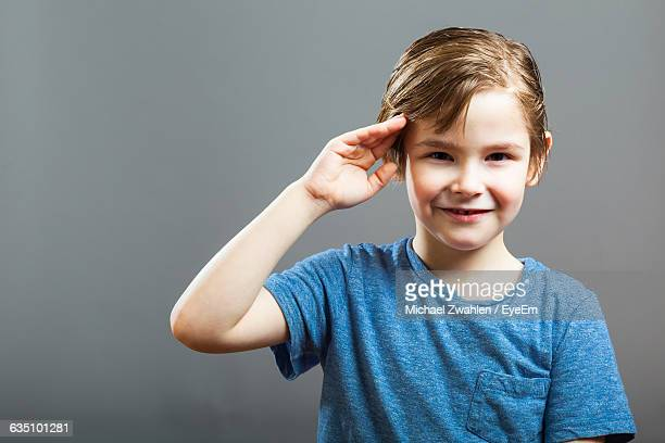 Portrait Of Smiling Boy Saluting Against Gray Background
