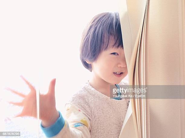 Portrait Of Smiling Boy Seen Through Glass Window