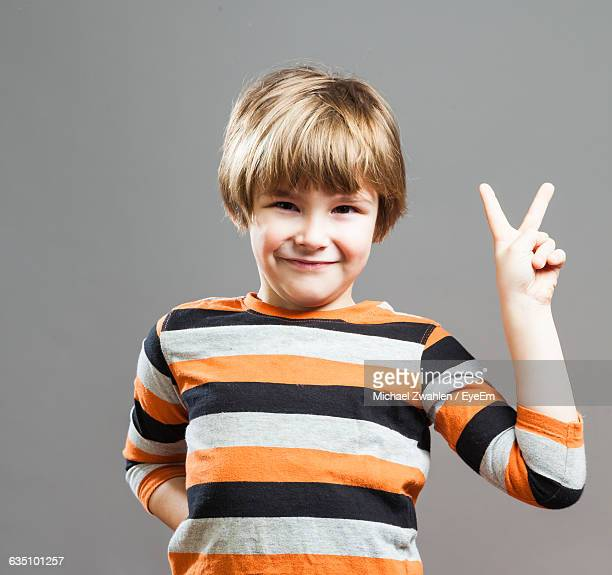 Portrait Of Smiling Boy Showing Peace Sign Against Gray Background