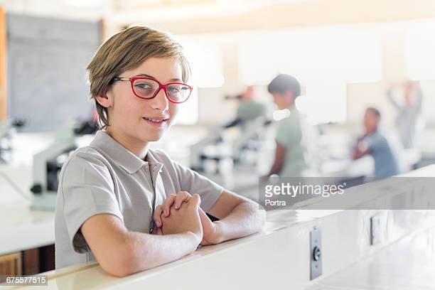 Portrait of smiling boy sitting at desk in class