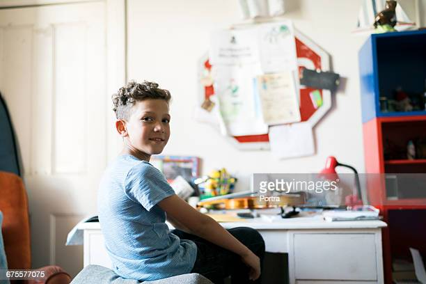 Portrait of smiling boy sitting in room at home