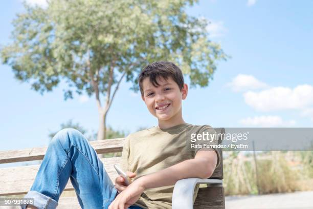 Portrait Of Smiling Boy Sitting On Bench Against Sky