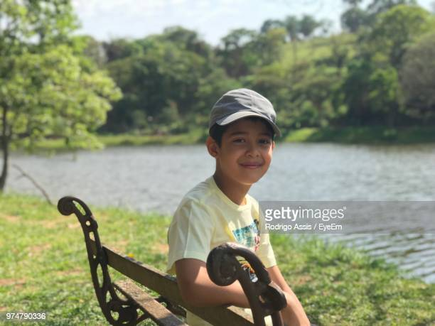 portrait of smiling boy sitting on bench by river - assis ストックフォトと画像