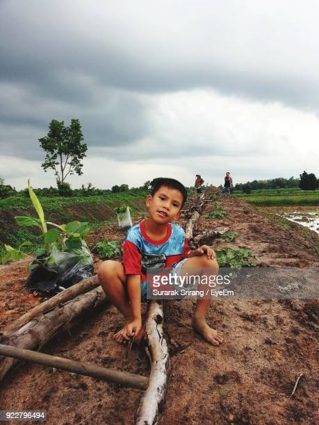 Portrait Of Smiling Boy Sitting On Field Against Cloudy Sky