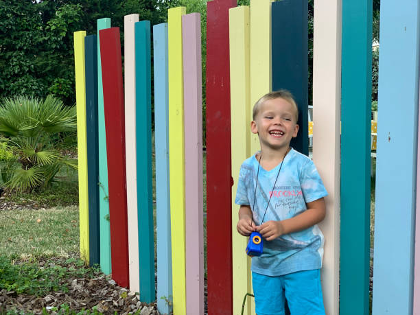 Portrait Of Smiling Boy Standing Against Color Wall