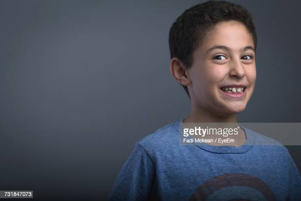 Portrait Of Smiling Boy Standing Against Gray Background