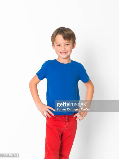 portrait of smiling boy standing against white background - one boy only stock pictures, royalty-free photos & images