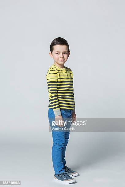 portrait of smiling boy standing against white background - stare in piedi foto e immagini stock