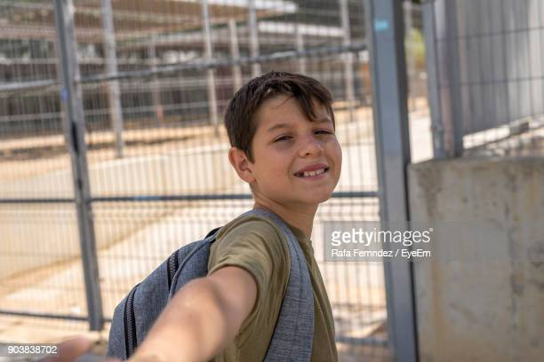 Portrait Of Smiling Boy Standing By Fence In Schoolyard