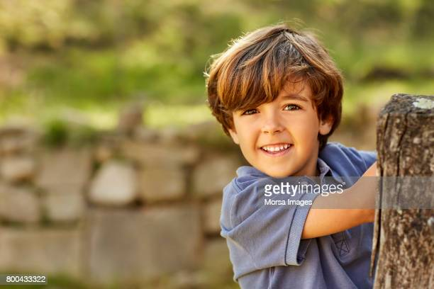 Portrait of smiling boy standing by post in yard