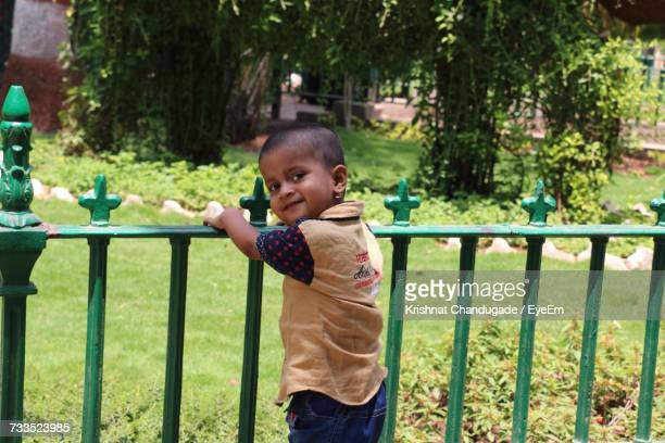 Portrait Of Smiling Boy Standing By Railing At Park