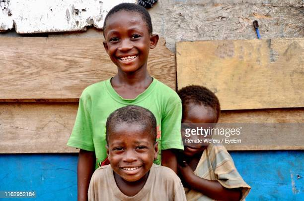 portrait of smiling boy standing by wooden house - ghana africa fotografías e imágenes de stock