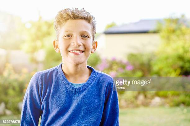 Portrait of smiling boy standing in park