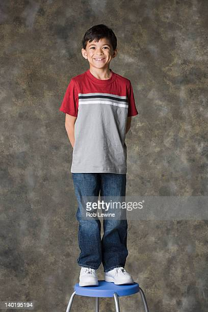 Portrait of smiling boy (8-9) standing on stool, studio shot