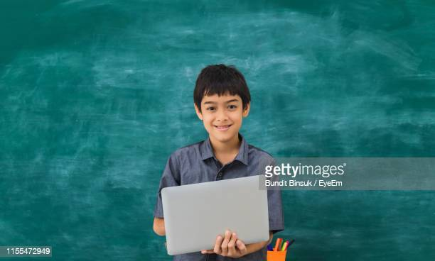 portrait of smiling boy using laptop against blackboard in school - one boy only stock pictures, royalty-free photos & images