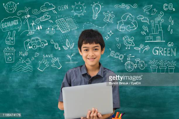 portrait of smiling boy using laptop against drawing on blackboard in school - one boy only stock pictures, royalty-free photos & images
