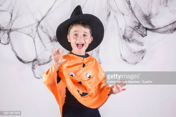 Portrait Of Smiling Boy Wearing Costume While Standing Against White Background During Halloween