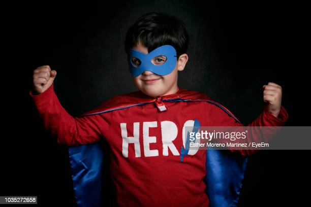 portrait of smiling boy wearing eye mask and cape standing against black background - black mask disguise stock pictures, royalty-free photos & images