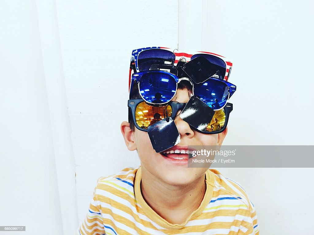 Portrait Of Smiling Boy Wearing Various Sunglasses Against Wall : Stock Photo