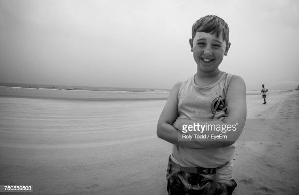 Portrait Of Smiling Boy With Arms Crossed Standing On Sand At Daytona Beach