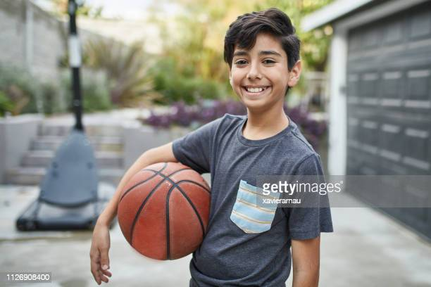 retrato de niño sonriente con la situación del baloncesto en yarda - 10 11 años fotografías e imágenes de stock