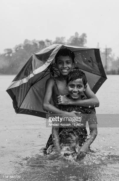 portrait of smiling boy with brother in lake during rainy season - amdad hossain stock pictures, royalty-free photos & images
