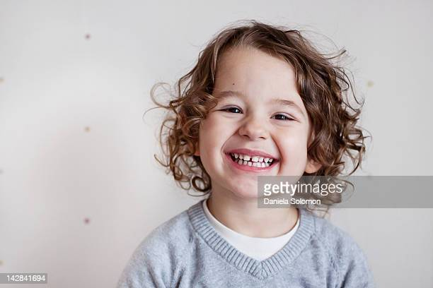 portrait of smiling boy with curly brown hair - vorschulkind stock-fotos und bilder