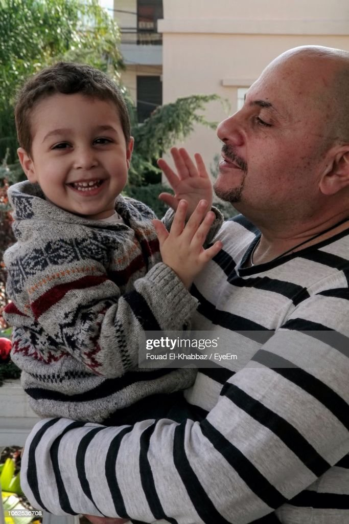 Portrait Of Smiling Boy With Father Outdoors : Stock Photo