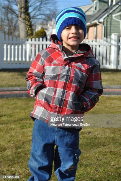 portrait of smiling boy with hands in pockets standing on grassy field at back yard - meghan stock photos and pictures