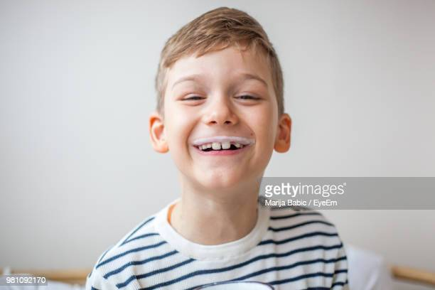 Portrait Of Smiling Boy With Milk Mustache Against Wall