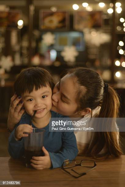 Portrait Of Smiling Boy With Mother Kissing Him