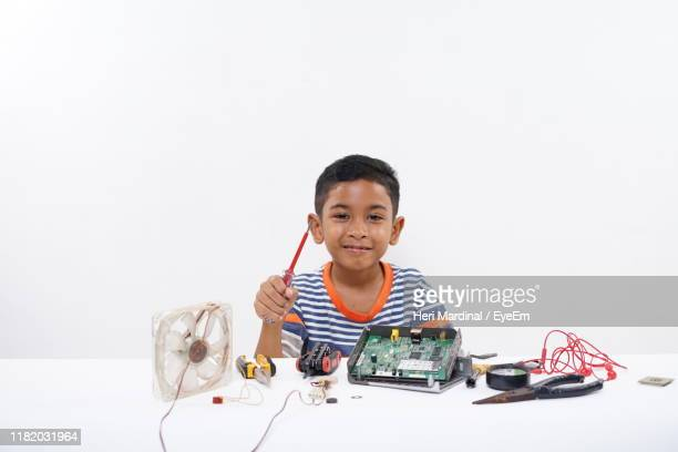 portrait of smiling boy with screwdriver sitting by circuit board over white background - heri mardinal stock pictures, royalty-free photos & images