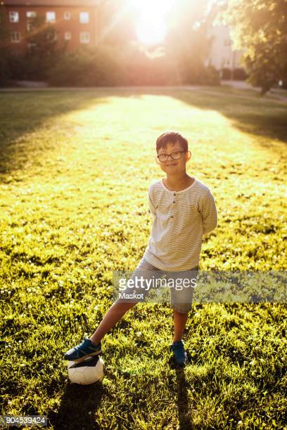 Portrait of smiling boy with soccer ball standing on grassy field at park