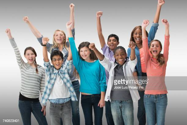 portrait of smiling boys and girls celebrating with raised arms - multiculturalismo foto e immagini stock