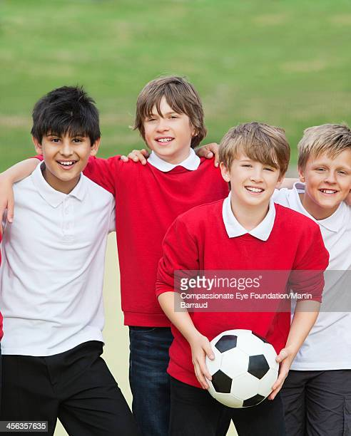 Portrait of smiling boys (10-11) with soccer ball