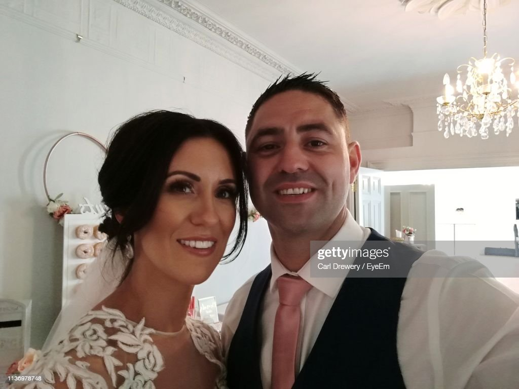 Portrait Of Smiling Bride And Bridegroom Standing At Home : Stock Photo