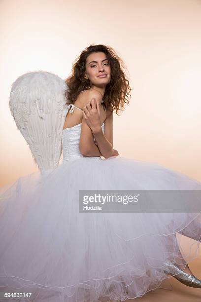 Portrait of smiling bride wearing angel wings against colored background